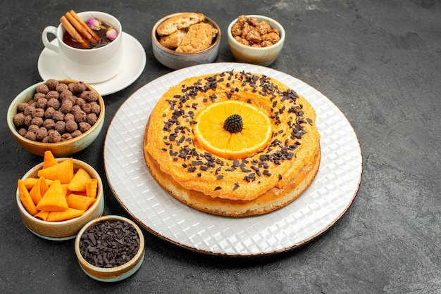 Front view delicious sweet pie with orange slices and cup of tea on dark background cookie pie biscuit dessert tea cake