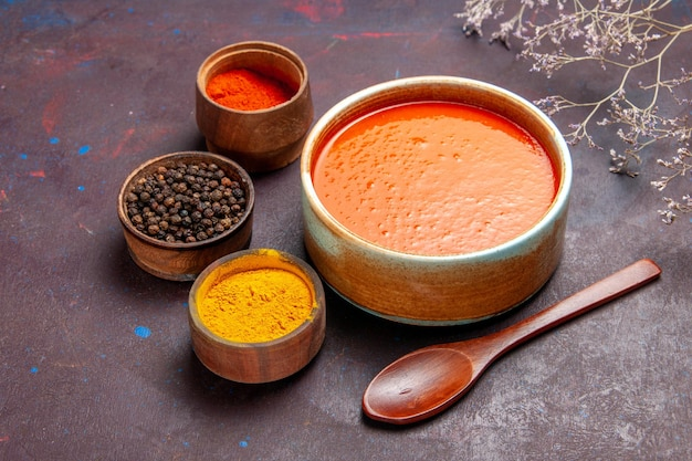 Vista frontale deliziosa zuppa di pomodoro cucinata con pomodori freschi con condimenti su spazio scuro