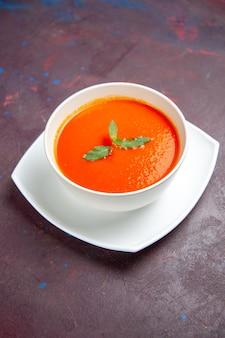 Vista frontale deliziosa zuppa di pomodoro piatto gustoso con una foglia all'interno del piatto su uno spazio buio