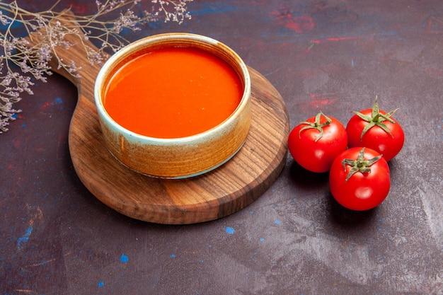 暗いスペースに新鮮なトマトを入れた正面のおいしいトマトスープ