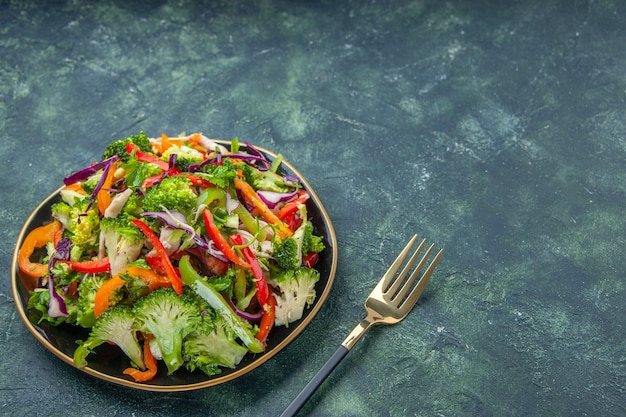 Vista frontale di una deliziosa insalata vegana in un piatto con varie verdure e forchetta sul lato destro su sfondo scuro con spazio libero