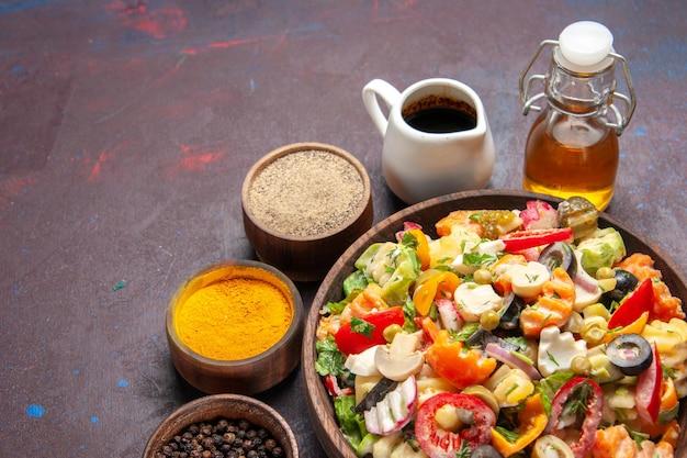 暗いスペースにスライスしたトマトのオリーブとマッシュルームの正面から見たおいしい野菜サラダ