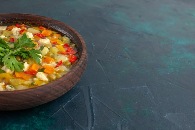 Vista frontale deliziosa zuppa di verdure con diversi ingredienti all'interno del piatto marrone sulla scrivania scura