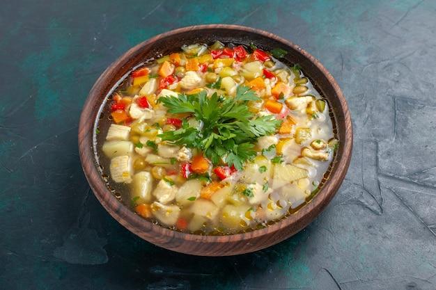 暗い机の上の茶色の鍋の中にさまざまな材料を使ったおいしい野菜スープの正面図