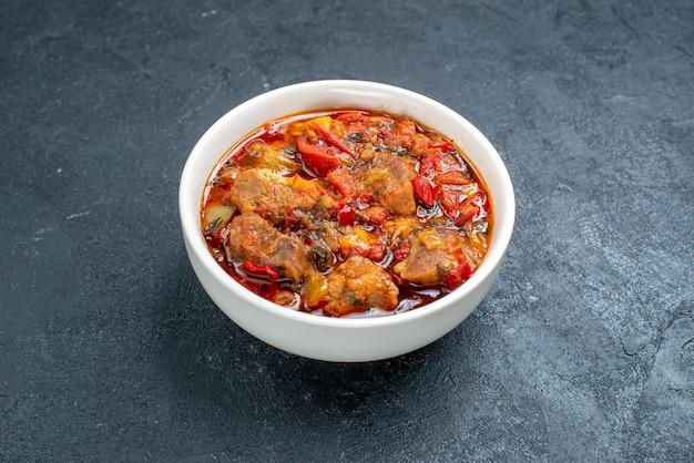 Вид спереди вкусный овощной суп с мясом внутри тарелки на сером пространстве