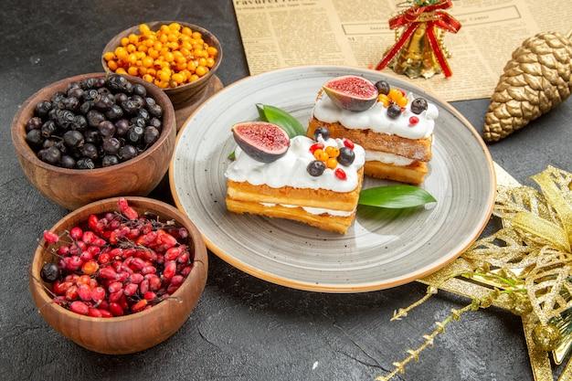 正面図暗い背景にフルーツとおいしいワッフルケーキ甘いケーキフォトクリームデザート