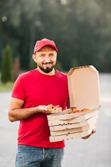 Front view delivery guy holding a pizza slice