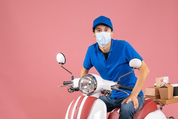Vista frontale del ragazzo delle consegne in maschera medica che indossa un cappello seduto su uno scooter su sfondo color pesca pastello