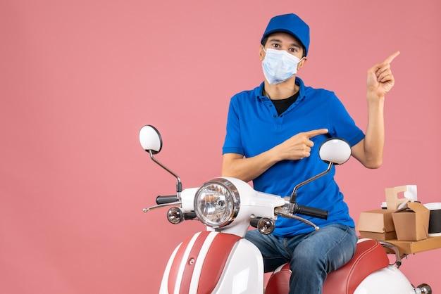 Vista frontale del ragazzo delle consegne in maschera medica che indossa un cappello seduto su uno scooter che punta qualcosa sul lato sinistro su sfondo color pesca pastello