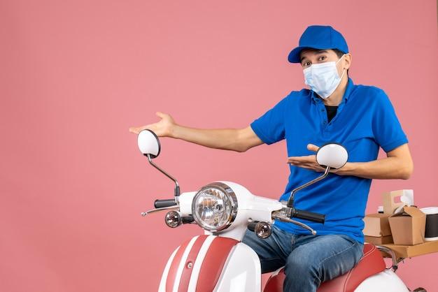 Vista frontale del ragazzo delle consegne in maschera medica che indossa un cappello seduto su uno scooter che punta qualcosa sul lato destro su sfondo color pesca pastello