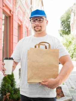Front view delivery guy with bag and coffee