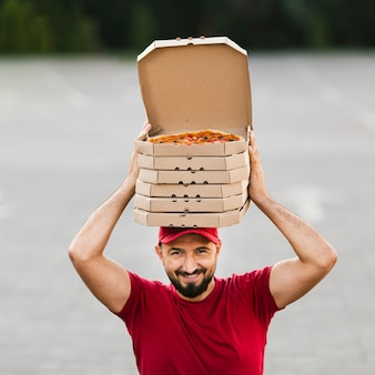 Front view delivery guy with pizza boxes on his head