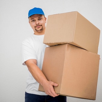 Front view delivery man holding boxes