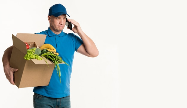 Front view of delivery man holding grocery box and smartphone