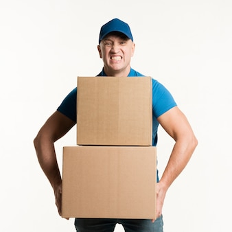 Front view of delivery man holding heavy cardboard boxes