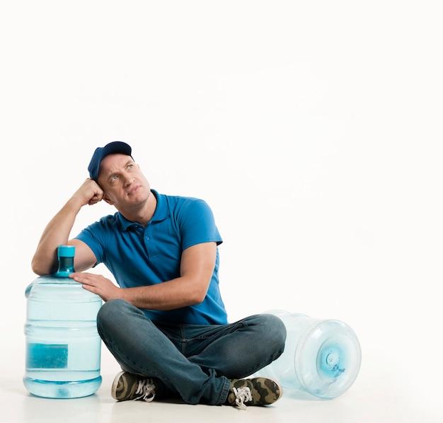 Vista frontale del fattorino che posa con la bottiglia di acqua