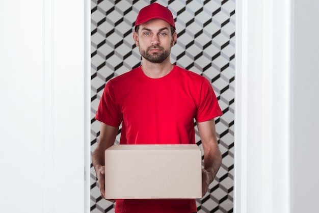 Front view delivery man wearing red uniform