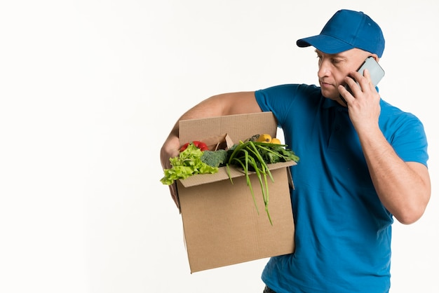 Front view of delivery man with smartphone and grocery box