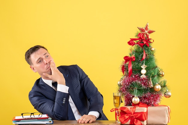Front view of depresed man putting hand on his cheek sitting at the table near xmas tree and presents on yellow