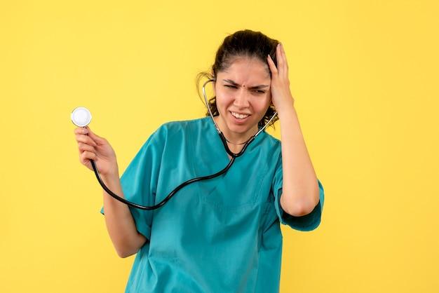Stetoscopio femminile depresso della tenuta del medico di vista frontale che mette la mano alla sua testa che sta su fondo giallo