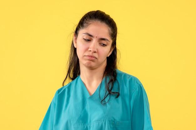 黄色の背景に立っている正面図落ち込んでいる女性医師