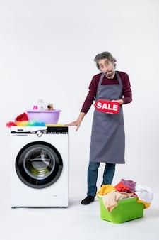 Вид спереди подавленный парень в фартуке, держащий знак продажи, стоящий возле стиральной машины на белом фоне