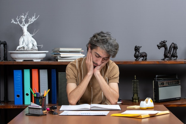 Front view depressed office worker sitting at table