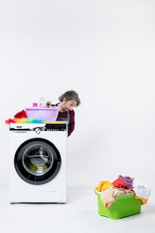 Front view depressed young man in apron sitting behind washer laundry basket on white background