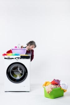 Вид спереди подавленный молодой человек в фартуке, сидящий за корзиной для белья стиральной машины на белом фоне