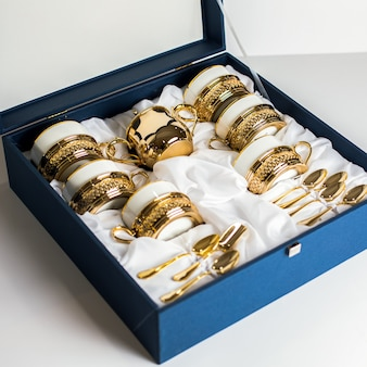 A front view designed cutlery white-gold colored glasses cups spoons inside blue box on the white background
