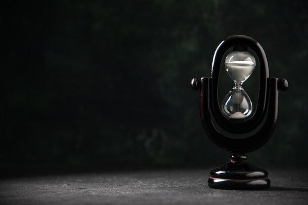 전면보기는 어두운 표면에 검은 색 모래 시계를 디자인했습니다.