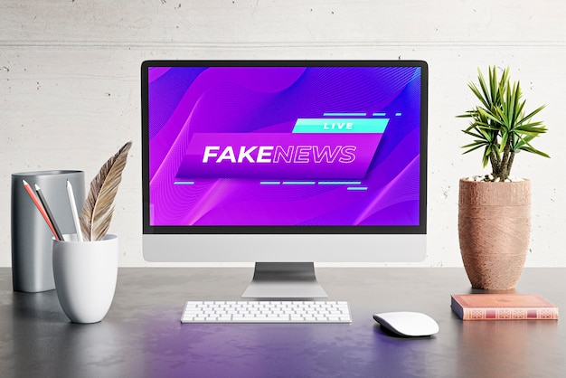 Front view of desk with computer and fake news