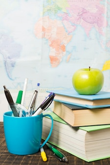 Front view of desk with school supplies and an apple