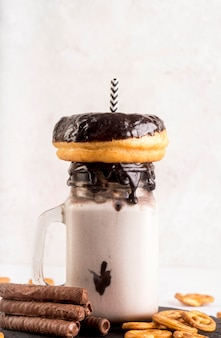 Vista frontale del dessert in barattolo con ciambella e paglia