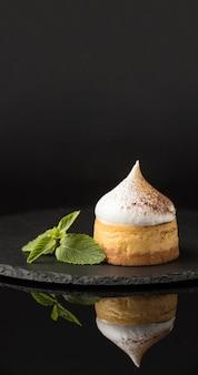 Vista frontale del dessert su ardesia con menta e cacao in polvere