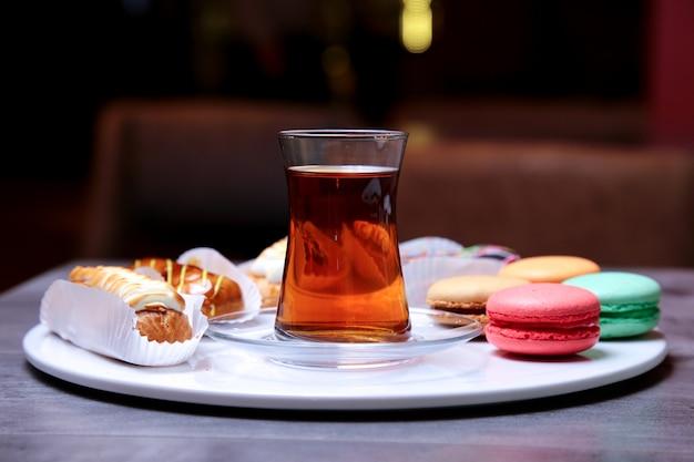 Вид спереди на десерты с шоколадной карамелью и сливками, эклеры с печеньем макарон на тарелке с чаем в стакане армуда