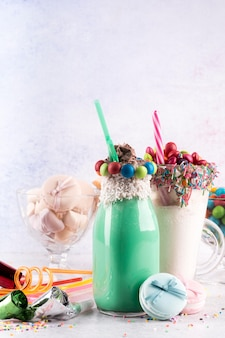 Front view of desserts with colorful candy and straws
