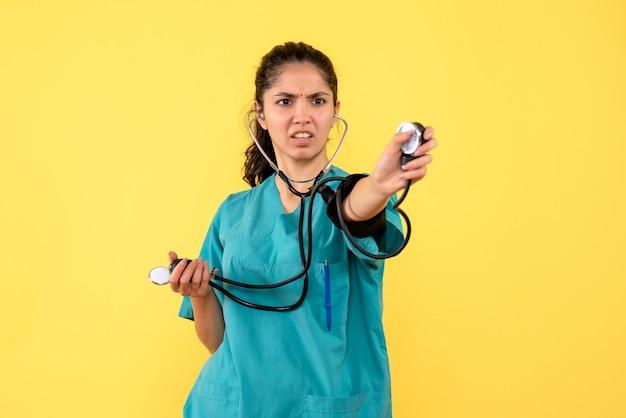 Vista frontale determinata medico femminile in uniforme che tiene sfigmomanometri in piedi su sfondo giallo isolato