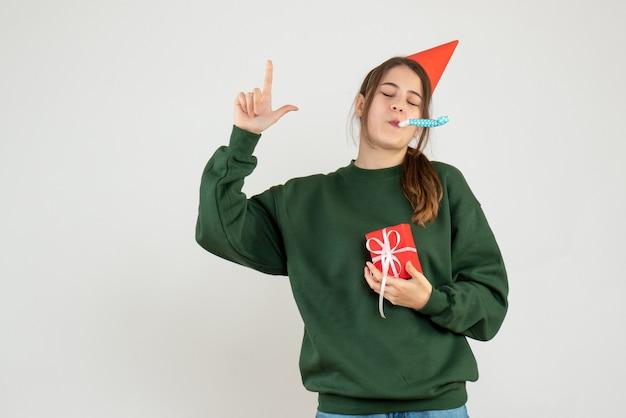 전면보기는 소음기를 사용하여 손가락으로 가리키는 파티 모자로 소녀를 결정했습니다.