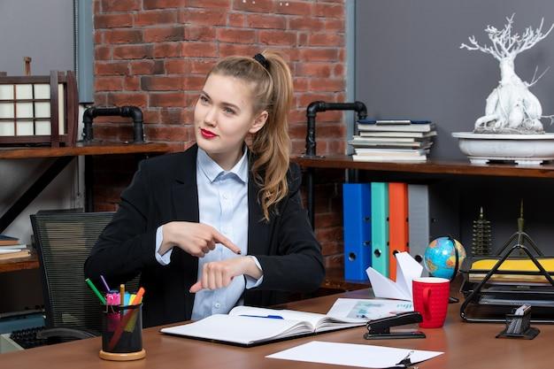 Vista frontale di una giovane donna determinata seduta a un tavolo e che indica il suo tempo in ufficio