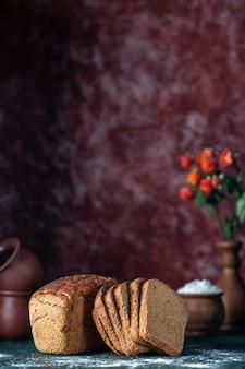Vista frontale del pane nero dietetico e del vaso di fiori di farina delle ciotole su sfondo blu marrone rossiccio