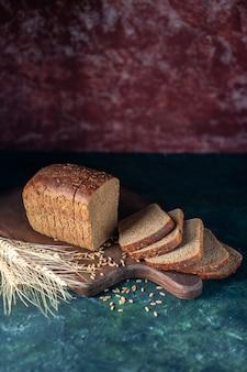 Vista frontale delle punte di pane nero dietetico su sfondo blu marrone rossiccio