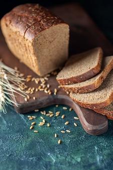 La vista frontale del pane nero dietetico picchia i grani sul tagliere di legno su sfondo blu scuro di colori