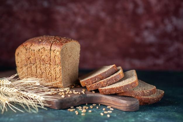 La vista frontale del pane nero dietetico picchia i grani sul tagliere di legno su fondo di colori misti marrone rossiccio blu