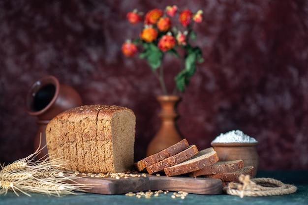 Vista frontale del pane nero dietetico picchi di grano su tagliere di legno ciotole vaso di fiori su sfondo blu marrone misti colori
