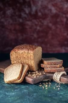 Vista frontale dei frumenti dietetici del pane nero sul tagliere di legno su fondo di colori misti marrone rossiccio blu