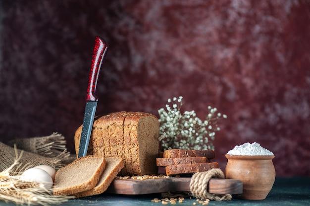Vista frontale dei grani di pane nero dietetico sul tagliere di legno coltello fiore uova farina in una ciotola asciugamano marrone su sfondo di colori misti