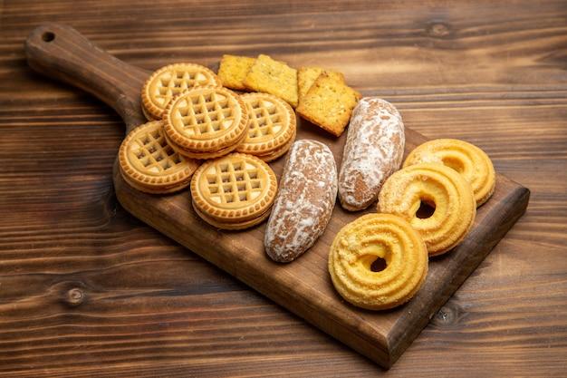 Вид спереди различные сладости печенья для чая на коричневом столе, печенье, бисквитном сахаре
