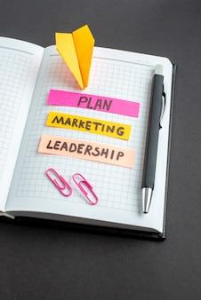 暗い背景のメモ帳でさまざまなビジネスノートを正面から見る