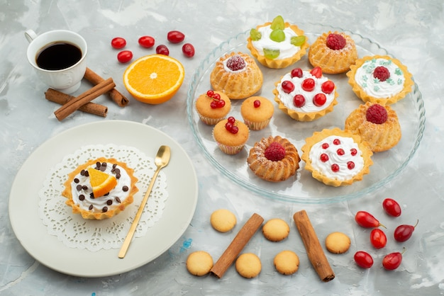 Front view different cakes with cookies cinnamon and cup of coffee on the light surface sugar sweet fruit